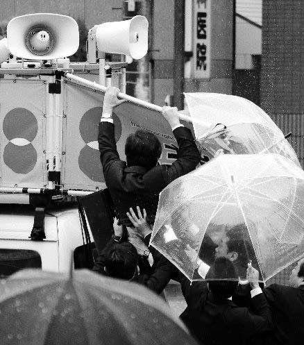 野田佳彦在攀登宣传车的梯子准备登上车顶讲演时,手没能抓住梯子,一下子摔了下来,幸有保镖在下面保护。